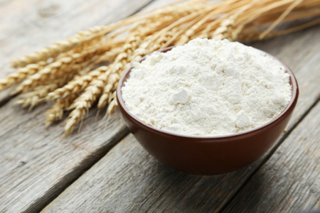spikelets: Bowl of wheat flour with spikelets on grey wooden background Stock Photo