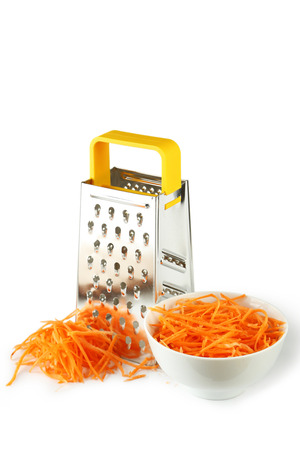 Metal grater and carrot isolated on white photo