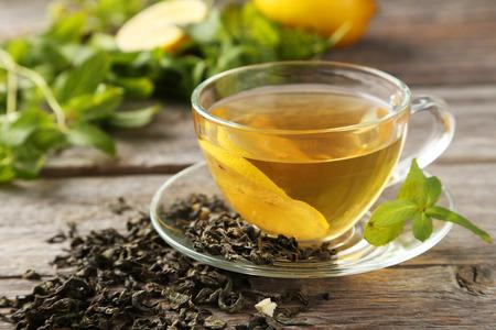 frutas secas: Taza con té verde sobre fondo de madera gris