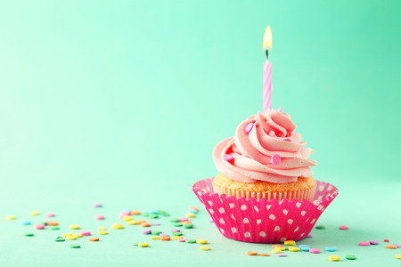 Tasty cupcake with candle on green background