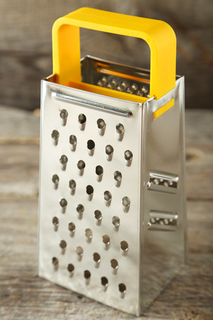 metal grater: Metal grater on grey wooden background Stock Photo