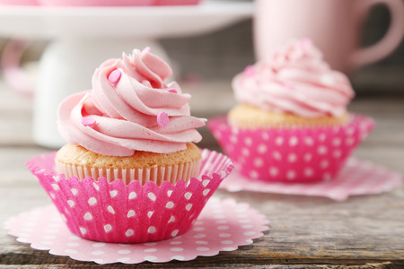 Tasty cupcake on grey wooden background