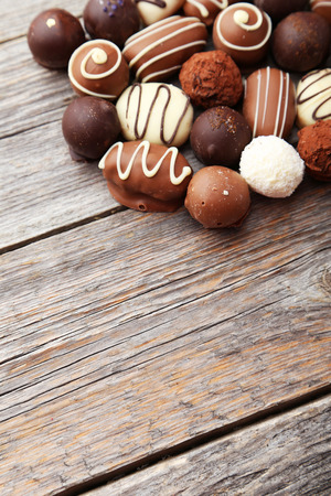 candy background: Chocolates on grey wooden background