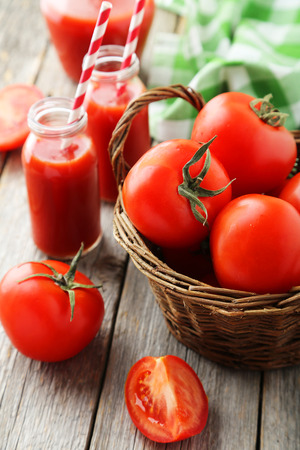 Fresh red tomatos in basket and juice in bottles on grey wooden background