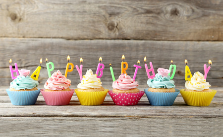 Birthday cupcakes with candles on grey wooden background