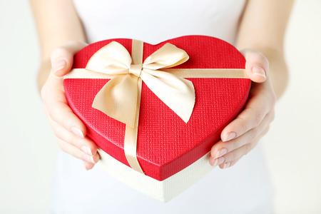 Female hands holding heart gift box