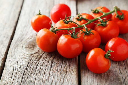 Fresh cherry tomatoes on grey wooden background