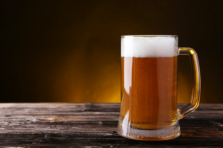Mug of beer on brown wooden background