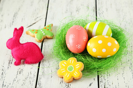 Easter eggs in nest on white wooden background photo