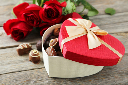 Beautiful heart gift box with chocolates on grey wooden background