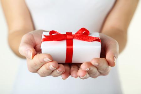 dando la mano: Manos femeninas que sostienen la caja de regalo