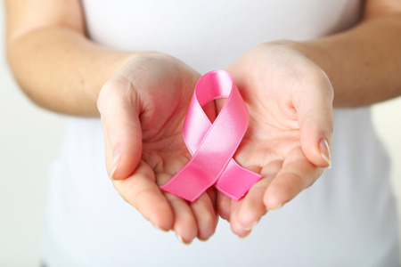 nice breast: Female hands holding pink ribbon, healthcare and medicine concept