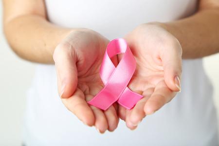 cancer de mama: Manos femeninas que sostienen la cinta rosada, salud y concepto de la medicina