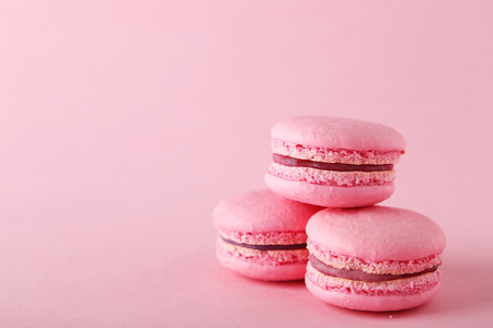 sweet foods: French pink macarons on pink background Stock Photo