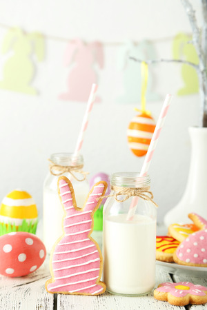 dairying: Easter cookies with bottle of milk on white wooden background