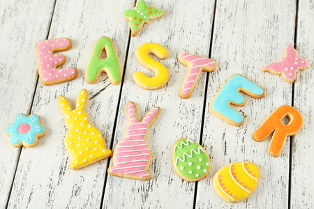Colorful easter cookies on white wooden background photo