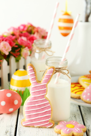 Easter cookies with bottle of milk on white wooden background photo