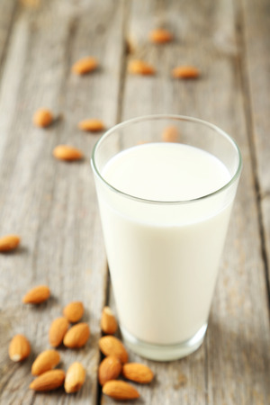 dairying: Glass of milk with almonds on grey wooden background