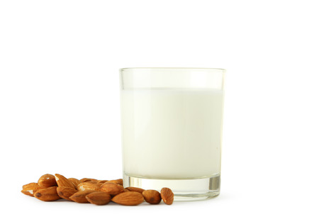 dairying: Glass of milk with almonds isolated on white