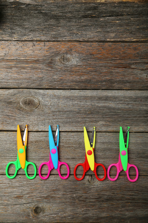 figured: Figured scissors on grey wooden background