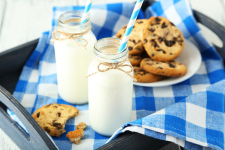 dairying: Two bottles of milk with striped straws and plate of cookies on white wooden background
