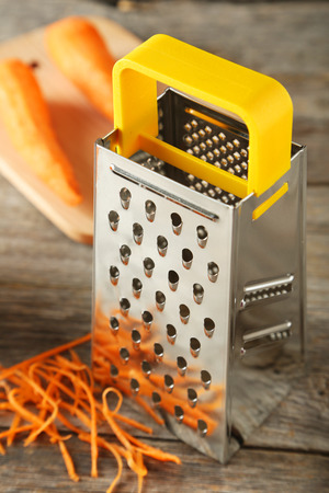 metal grater: Metal grater and carrot on grey wooden background