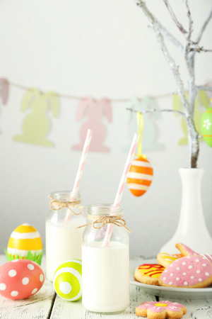 Easter cookies with bottle of milk on white wooden background