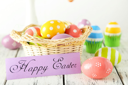 Easter eggs in basket on white wooden background photo