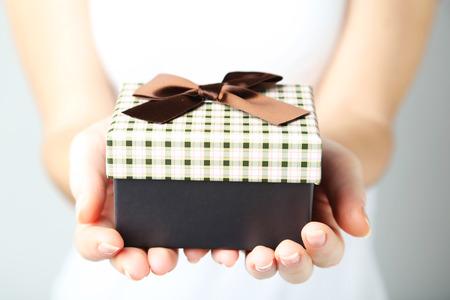 cajas navide�as: Manos femeninas que sostienen la caja de regalo