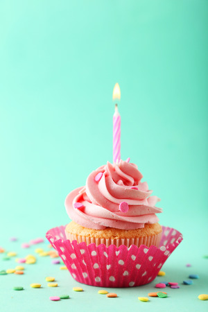 party food: Tasty cupcake with candle on green background