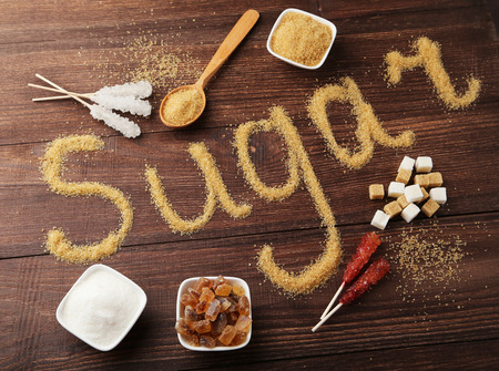 hyperglycemia: Various kinds of sugar on brown wooden background
