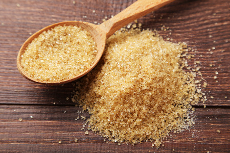 hyperglycemia: Brown sugar in spoon on brown wooden background