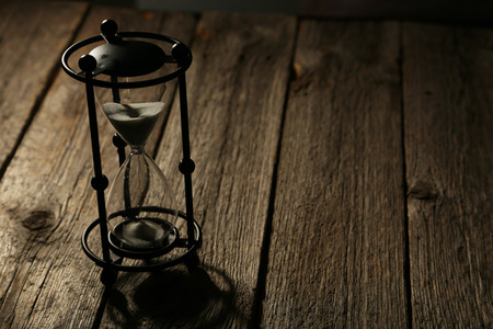 Black hourglass on grey wooden background photo