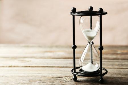 reloj de arena: Reloj de arena negro sobre fondo de madera gris