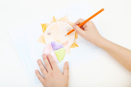 Childs hands drawing on a white paper photo