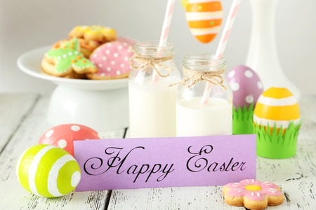 Easter cookies and eggs with bottle of milk on white wooden background photo
