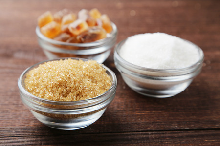 hyperglycemia: Various kinds of sugar in bowl on brown wooden background
