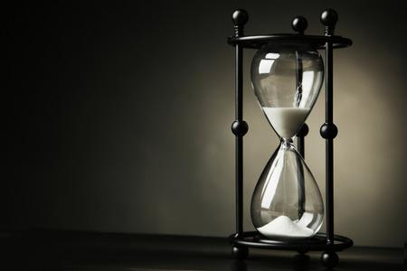 Black hourglass on black background photo