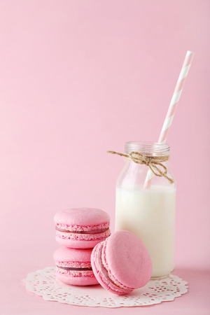 French macarons with bottle of milk on pink background photo