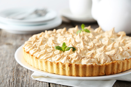 recipe decorated: Lemon meringue pie on plate on grey wooden background