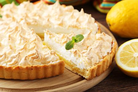 sweet tart: Lemon meringue pie on cutting board on brown wooden background