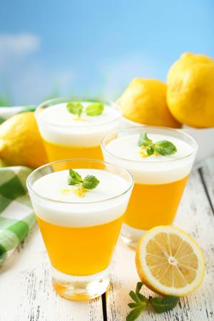 Tasty lemon jelly in glass on white wooden background photo