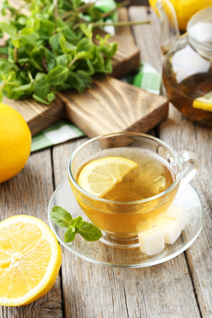 Cup of tea with mint and lemon on grey wooden background photo