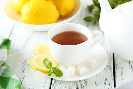 Cup of tea with mint and lemon on white wooden background photo