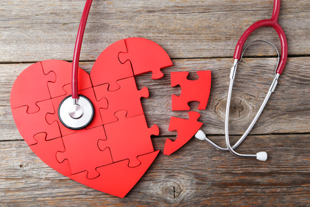 Red puzzle heart with stethoscope on grey wooden background photo