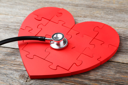murmur: Red puzzle heart with stethoscope on grey wooden background