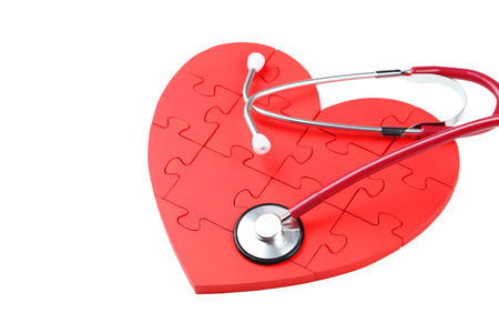 Red puzzle heart with stethoscope isolated on white photo