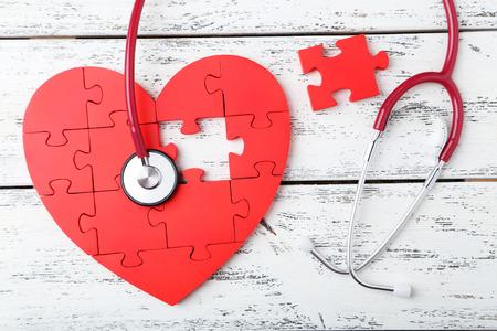 estetoscopio corazon: Coraz�n rojo del rompecabezas con el estetoscopio en el fondo de madera blanca