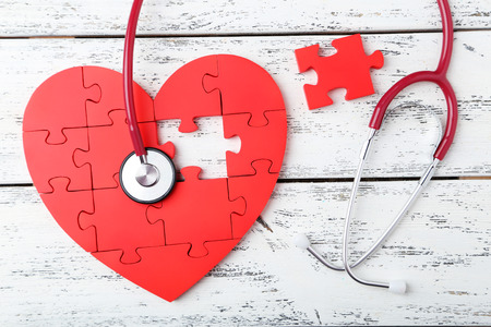 Red puzzle heart with stethoscope on white wooden background photo