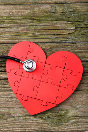 Red puzzle heart with stethoscope on wooden background photo